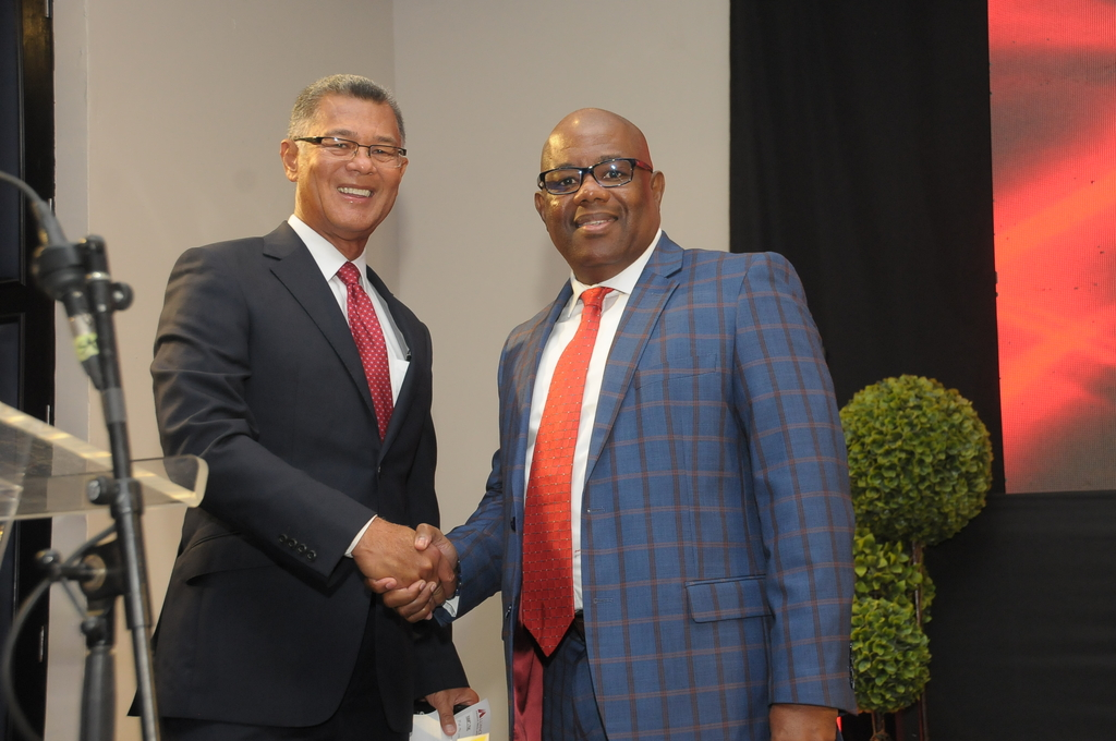 Peter Chin (left), chairman and CEO, Alliance Financial Services Limited (AFSL) and Karl Townsend, chief country officer (Jamaica) of JMMB Group Limited's capital markets unit shakes on the upcoming AFSL IPO, to be brokered by JMMB Securities Limited, subject to regulatory approval.