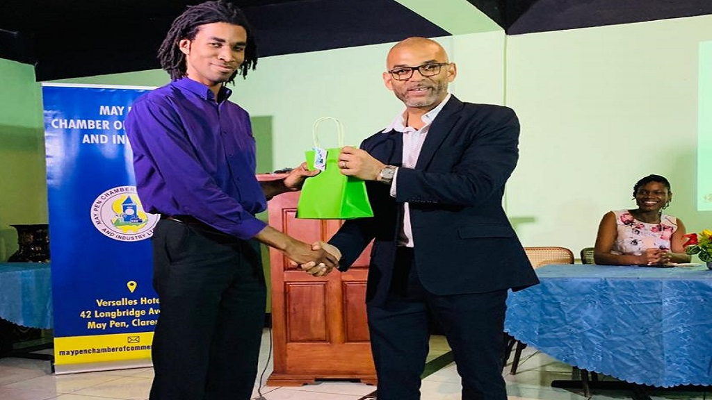 Gabriel Heron, VP – Marketing, JAMPRO (centre), presents a token to a participant at a recently held event at the May Pen Chamber of Commerce. Observing this presentation is Winsome Witter, President of the chamber (right).