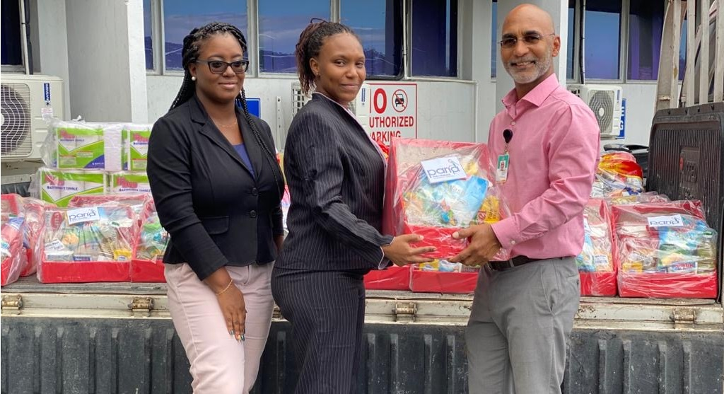 Caring 4 Community Foundation Trustee, Tiffany Robertson-Lara and President Genneil Nelson receive hamper from Paria Terminal Operations Manager, Collin Piper. .