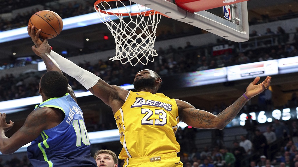 Dallas Mavericks forward Dorian Finney-Smith (10) tries to defend against a shot by Los Angeles Lakers forward LeBron James (23) during the second half of an NBA basketball game Friday, Jan. 10, 2020, in Dallas. (AP Photo/Richard W. Rodriguez).
