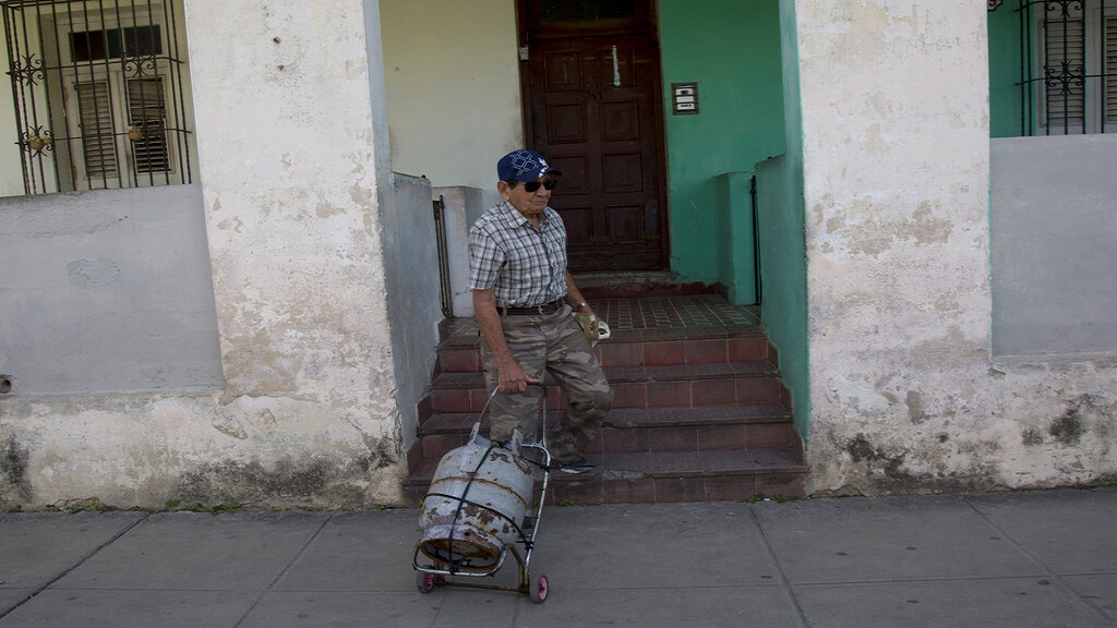 Alberto Perez, a 77-year-old retired man, leaves his home in the Sevillano neighborhood with an empty cooking gas tank as he departs for a shop where he will replace it with a full one in Havana, Cuba, Tuesday, Jan 14, 2020. The Cuban government is warning citizens to prepare for shortages of cooking gas due to Trump administration sanctions on the island. (AP Photo/Ismael Francisco)