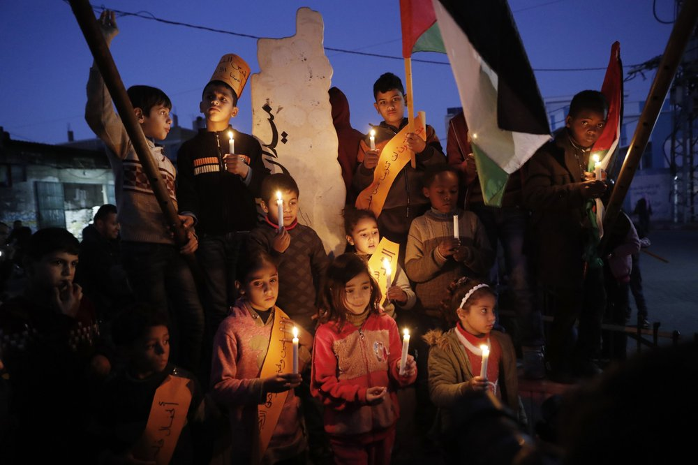 Protesters hold light candles as others wave their national flags during a protest against the Mideast plan announced by the U.S. President Donald Trump, at Jebaliya refugee camp, Gaza Strip, Thursday, January 30, 2020. (AP Photo/Adel Hana)