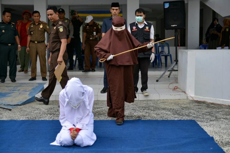 Une éxécutrice sur le point de flageller en public une femme agenouillée, le 10 décembre 2019 à Aceh, en Indonésie