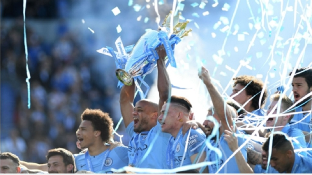 Manchester City celebrate with the Premier League trophy.