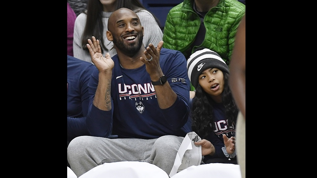 In this March 2, 2019 photo, Kobe Bryant and his daughter Gianna watch the first half of an NCAA college basketball game between Connecticut and Houston in Storrs, Conn. (AP Photo/Jessica Hill)