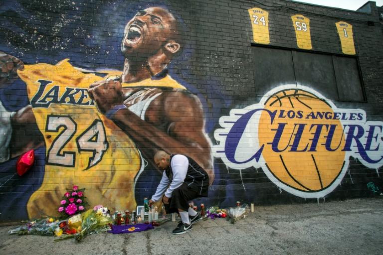 Un homme alume une bougie devant une fresque murale représentant Kobe Bryant à Los Angeles, le 26 janvier 2020, peu après l'annonce de la mort accidentelle de l'ancien joueur de basket. AFP / Apu GOMES