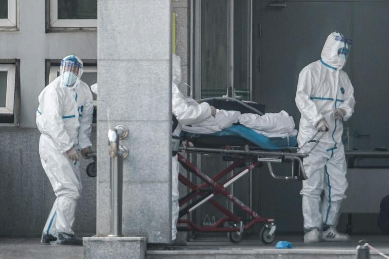 Des agents sanitaires transportent un malade dans un hôpital où sont soignés des patients infectés par un mystérieux virus analogue au Sras, le 18 janvier 2020 à Wuhan, en Chine. AFP / STR