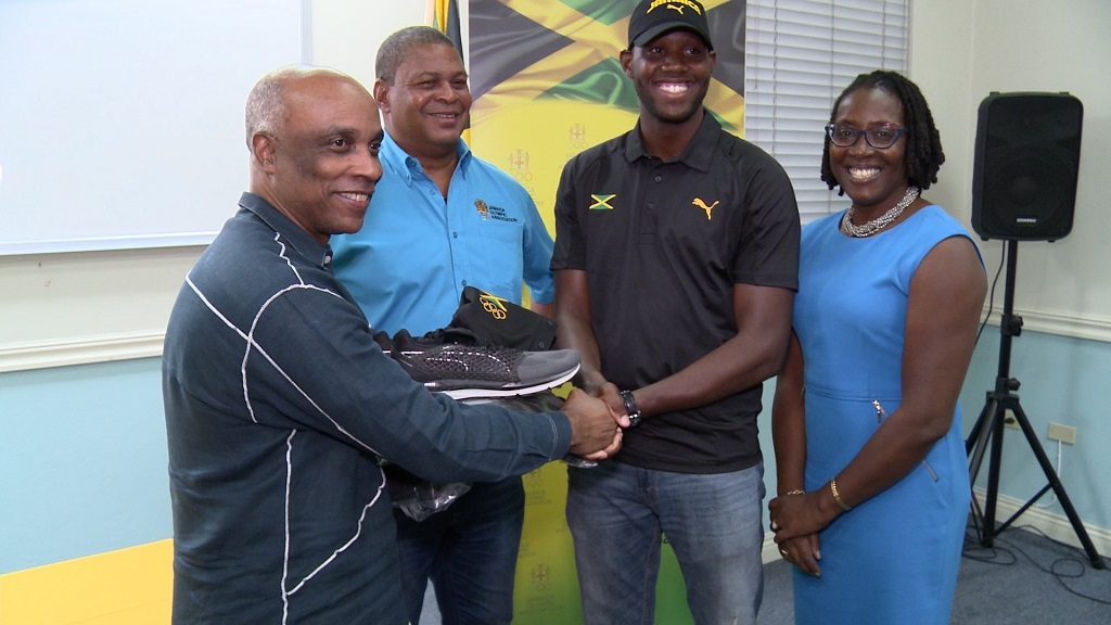 President of the Jamaica Olympic Association (JOA) Christopher Samuda (left), makes a presentation of gear to rower Shahiede Patterson (third left), while Jamaica Rowing Federation executives Robert Scott (second left) and Elaine Hayden (right) look on. The presentation took place at the JOA headquarters, Olympic Manor, in Kingston.