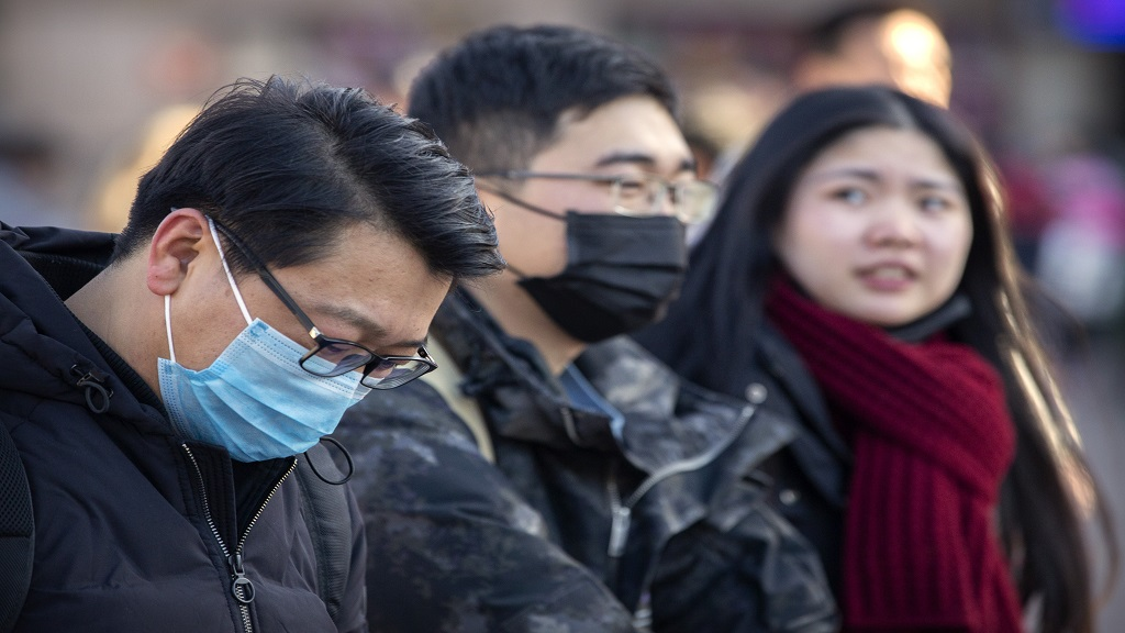Travelers wear face masks as they walk outside of the Beijing Railway Station in Beijing, Monday, January 20, 2020. China reported Monday a sharp rise in the number of people infected with a new coronavirus, including the first cases in the capital. The outbreak coincides with the country's busiest travel period, as millions board trains and planes for the Lunar New Year holidays. (AP Photo/Mark Schiefelbein)