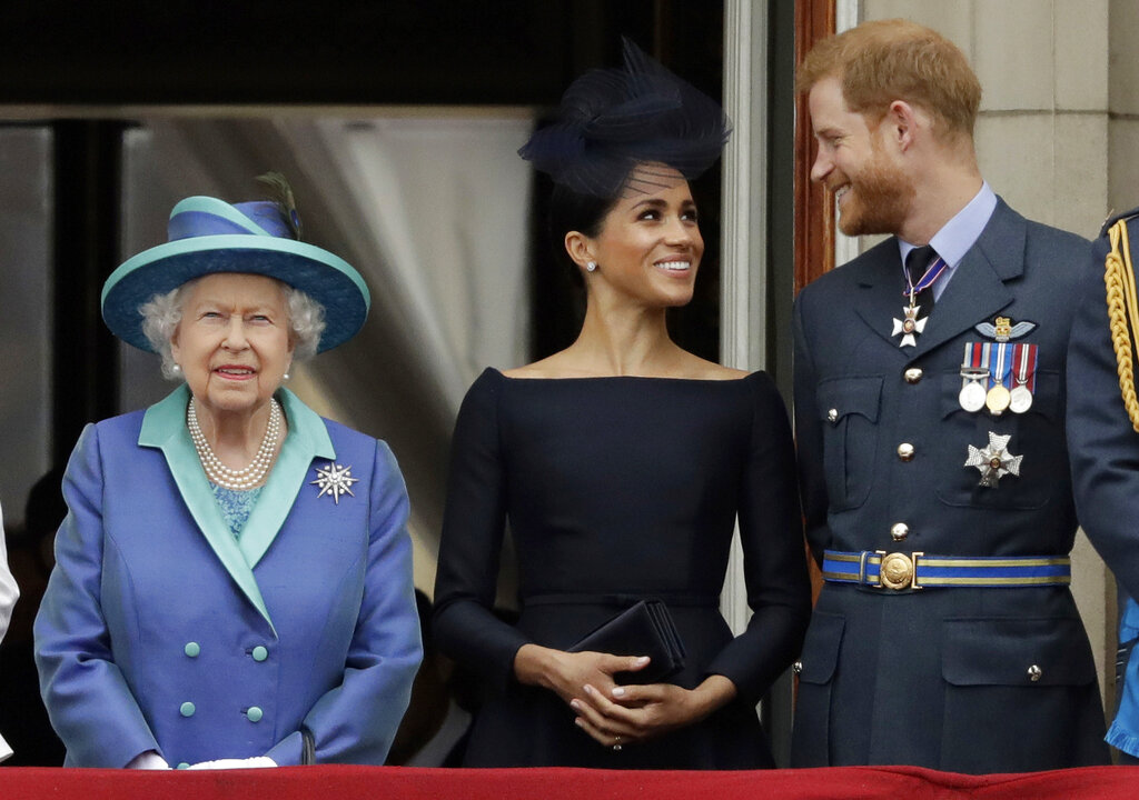 In this Tuesday, July 10, 2018 file photo Britain's Queen Elizabeth II, and Meghan the Duchess of Sussex and Prince Harry watch a flypast of Royal Air Force aircraft pass over Buckingham Palace in London. (AP Photo/Matt Dunham, File)