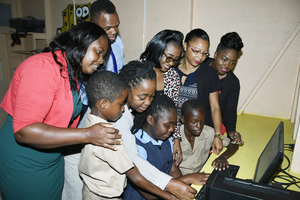 Students and teachers of New Works Primary School show their excitement on receiving computers from the JN Bank Member Advisory Council.