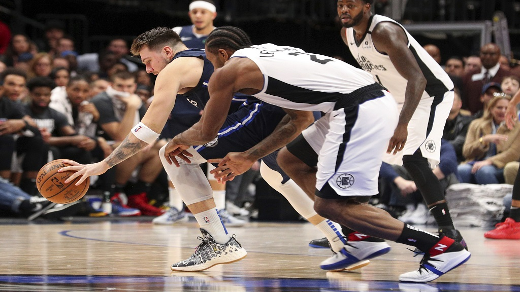 Dallas Mavericks forward Luka Doncic (77) and Los Angeles Clippers forward Kawhi Leonard (2) chase a loose ball during the second half of an NBA basketball game Tuesday, Jan. 21, 2020 in Dallas. (AP Photo/Richard W. Rodriguez).