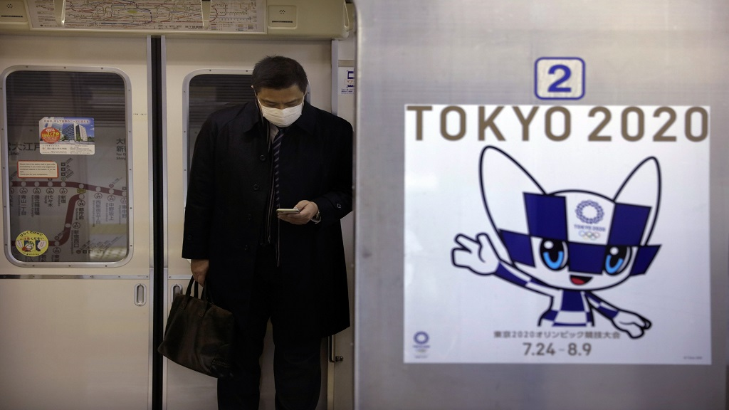 A poster promoting the Tokyo 2020 Olympics is posted next a train door as a commuter wearing a mask looks at his phone in a train, Friday, Jan. 31, 2020, in Tokyo.  (AP Photo/Jae C. Hong).