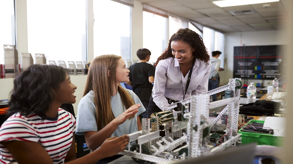 iStock photo of a teacher with female college students building a machine in Engineering class.