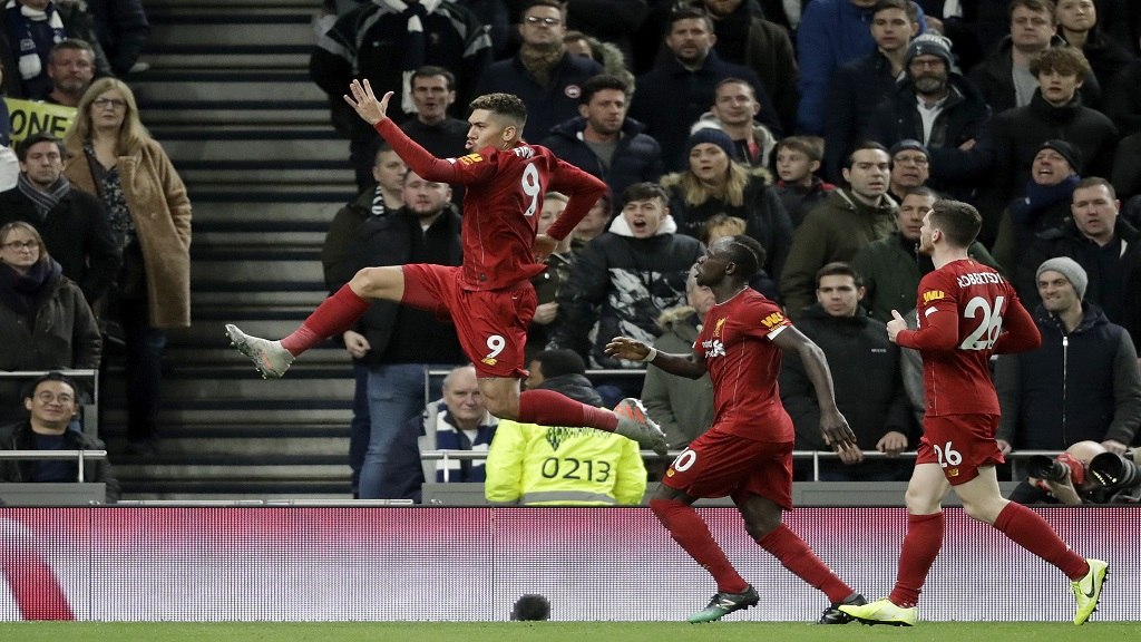 Liverpool's Roberto Firmino, left, celebrates after scoring against Tottenham during their English Premier League football match at the Tottenham Hotspur Stadium in London, England, Saturday, Jan. 11, 2020. (AP Photo/Matt Dunham).