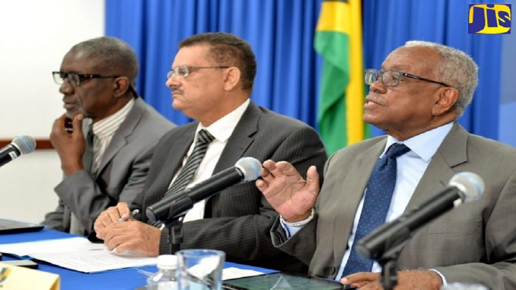 Then Chairman of the Integrity Commission, retired Justice Karl Harrison (right), responds to a question at a press conference on May 13, 2018 at the Planning Institute of Jamaica in St Andrew. Pictured listening were Commissioners Eric Crawford (left) and Dr Derrick McKoy. Both Harrison and McKoy have since left the commission.
