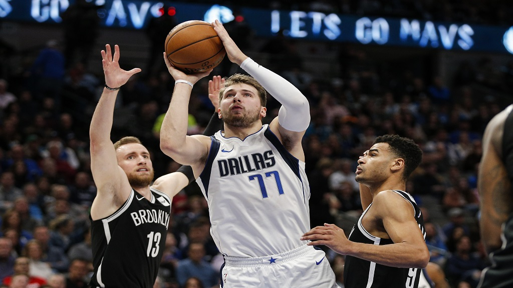 Dallas Mavericks forward Luka Doncic (77) attempts a shot as Brooklyn Nets guards Dzanan Musa (13) and Timothe Luwawu-Cabarrot (9) defend during the first half of an NBA basketball game Thursday, Jan. 2, 2020, in Dallas. (AP Photo/Brandon Wade).