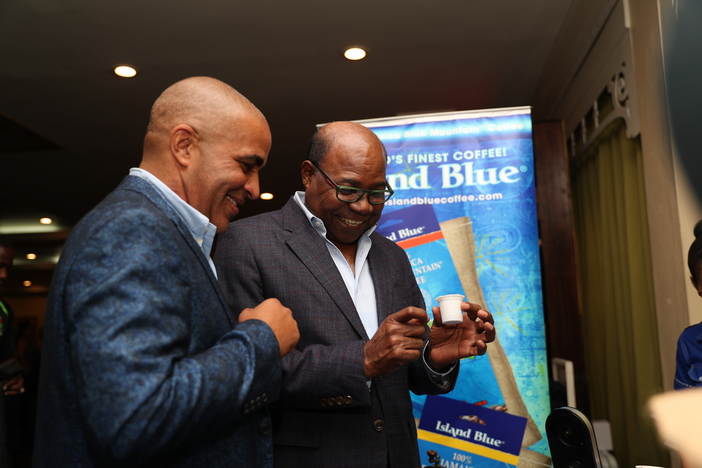 Tourism Minister Edmund Bartlett (right) examines a single-serve Island Blue Blue Mountain Coffee capsule as Jamaica Standard Products CEO John O Minott looks on.