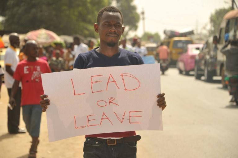 """Un manifestant brandit une pancarte """"Dirige ou pars"""", pour protester contre l'aggravation de la crise économique sous la direction de George Weah, le 6 janvier 2020 à Monrovia (Libéria) afp.com - Zoom DOSSO"""