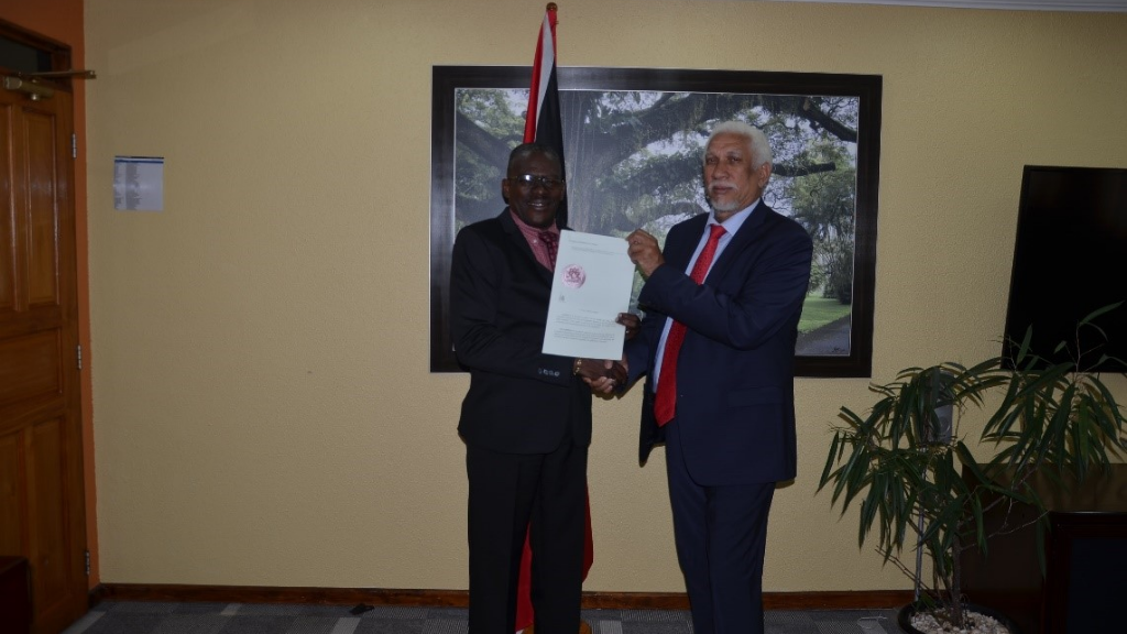 Housing Minister Edmund Dillon presents new HDC Chairman Noel Garcia with his Instrument of Appointment at the Minister's office on South Quay, PoS. Photo courtesy the Housing Development Corporation.
