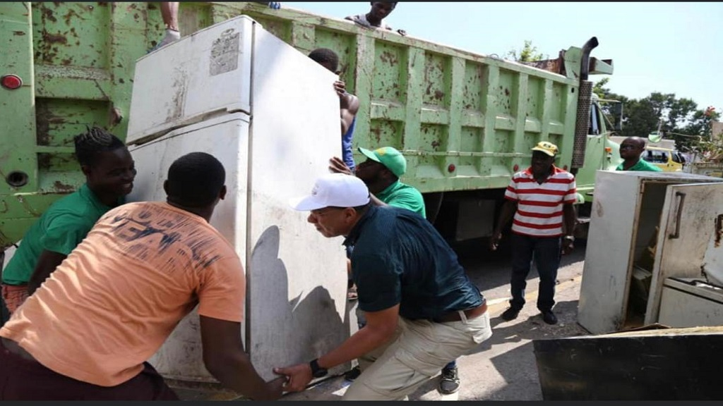 Prime Minister Andrew Holness (right lifting) assisting personnel to dispose of an old refrigerator  in the West Central St Andrew constituency that he represents in Parliament, during the National Dengue Clean-up effort on Saturday.