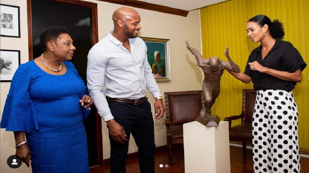 Former 100m world record holder Asafa Powell   (centre) admires his maquette along with wife, Alyshia, (right) and Sports Minister Olivia Grange.