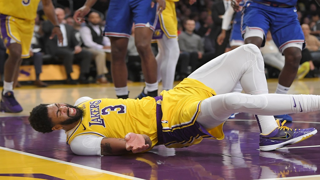 Los Angeles Lakers forward Anthony Davis winces as he hits the court after falling while trying to defend against a shot by New York Knicks forward Julius Randle during the second half of an NBA basketball game Tuesday, Jan. 7, 2020, in Los Angeles. Davis left the game. The Lakers won 117-87. (AP Photo/Mark J. Terrill).