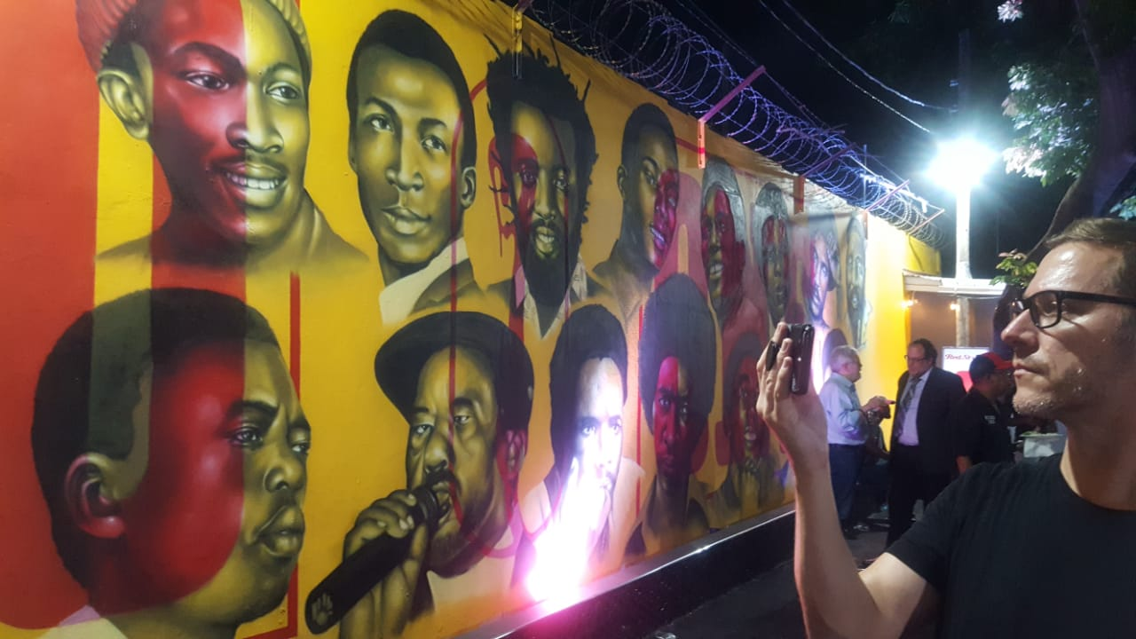 Alpha Boys' School Radio General Manager Joshua Chamberlain snaps a photo of the mural at StudioOne. (Photos: Marlon Reid)