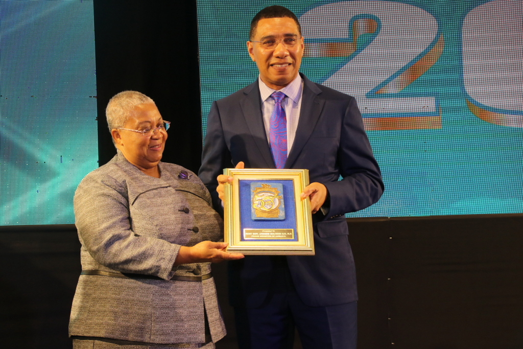 Prime Minister Andrew Holness accepts a token of appreciation from Jamaica Stock Exchange Managing Director, Marlene Street Forrest at the JSE's 15th Regional Investments and Capital Markets Conference on Tuesday.