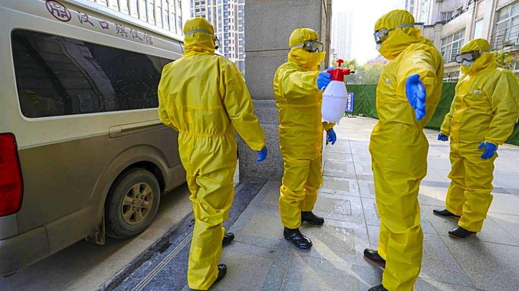 ILE - In this Jan. 30, 2020 file photo, funeral workers disinfect themselves after handling a virus victim in Wuhan in central China's Hubei Province, Thursday, Jan. 30, 2020. (Chinatopix via AP, File)