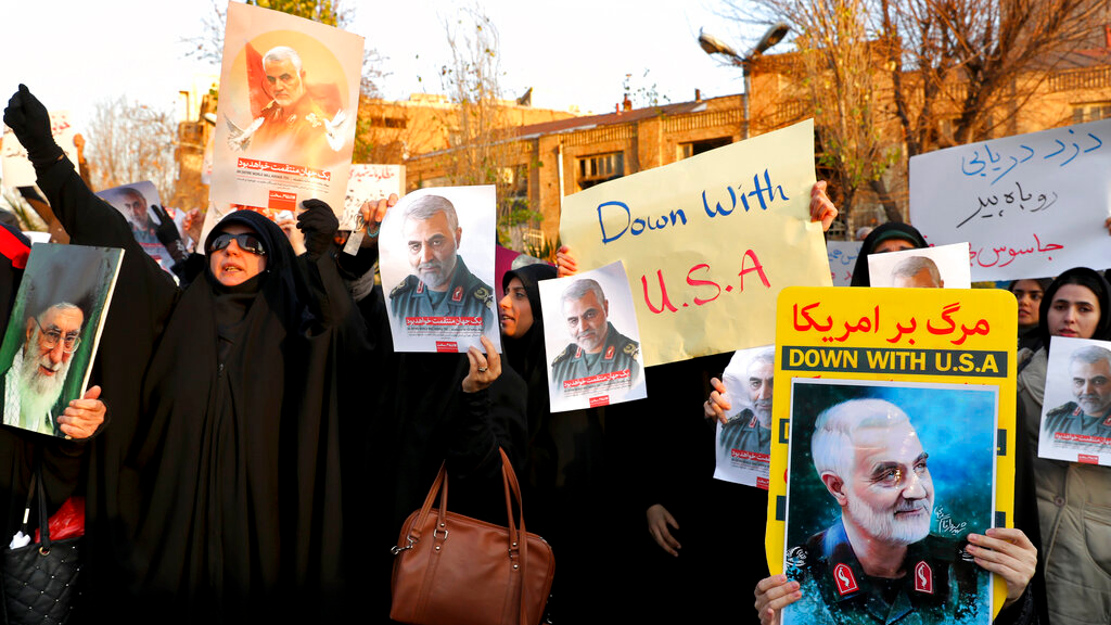 Protesters chant slogans and hold up posters of Gen. Qassem Soleimani during a demonstration in front of the British Embassy in Tehran, Iran, January 12, 2020. (AP Photo/Ebrahim Noroozi)