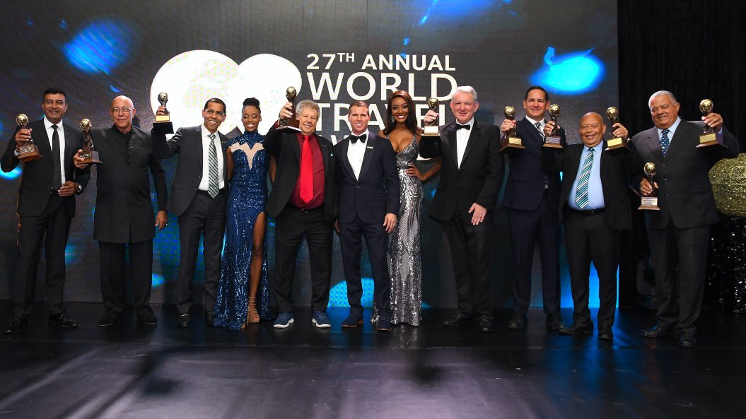 "General Managers of Sandals Resorts gather with the Honourable Gordon ""Butch"" Stewart and Adam Stewart to accept the award for the Caribbean's Leading Hotel Brand: Sandals Resorts International"