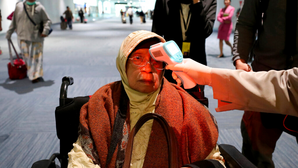 A health official scans the body temperature of a passenger as she arrives at the Soekarno-Hatta International Airport in Tangerang, Indonesia, Wednesday, January 22, 2020. Indonesia is screening travellers from overseas for a new type of coronavirus as fears spread about a mysterious infectious disease after its first death reported in China. (AP Photo/Tatan Syuflana)