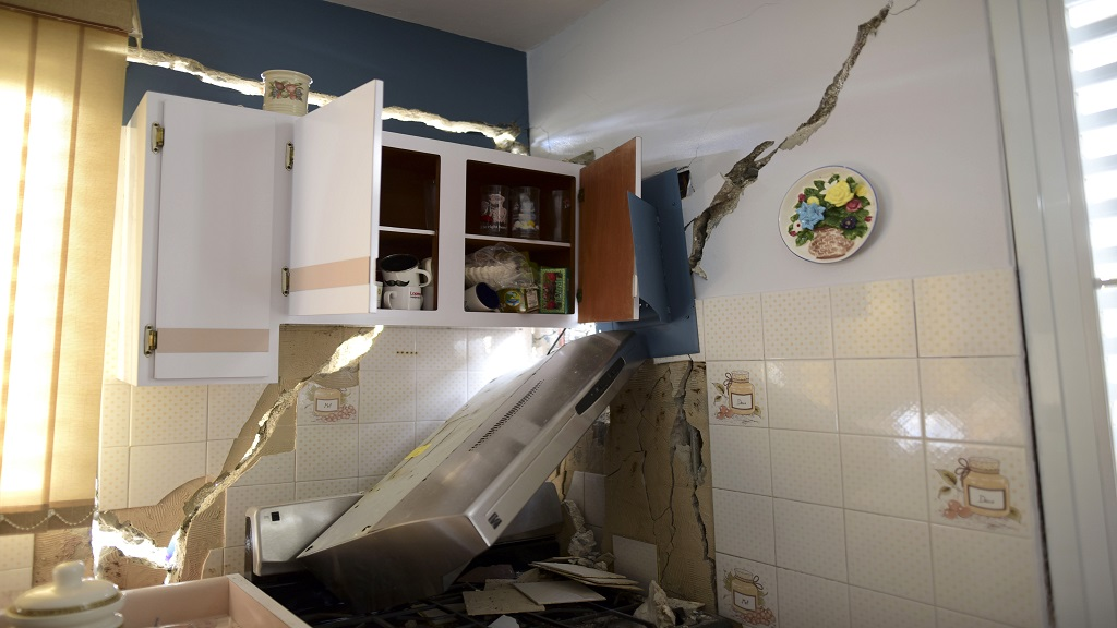The house of William Mercuchi is damaged after the previous day's magnitude 6.4 earthquake in Yauco, Puerto Rico, Wednesday, Jan. 8, 2020. (AP Photo/Carlos Giusti)