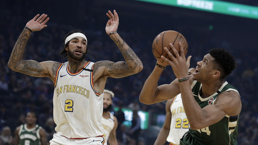 Milwaukee Bucks' Giannis Antetokounmpo, right, shoots as Golden State Warriors' Willie Cauley-Stein (2) defends during the first half of an NBA basketball game Wednesday, Jan. 8, 2020, in San Francisco. (AP Photo/Ben Margot).