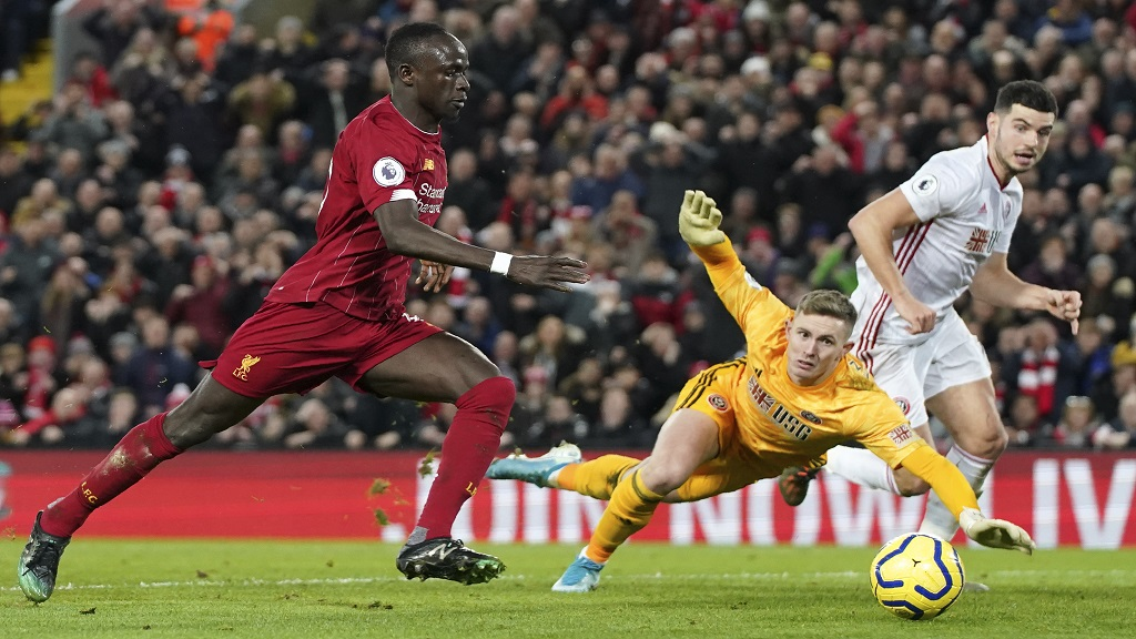 Liverpool's Sadio Mane, left, scores against Sheffield United during their English Premier League football match at Anfield Stadium, Liverpool, England, Thursday, Jan. 2, 2020. (AP Photo/Jon Super).