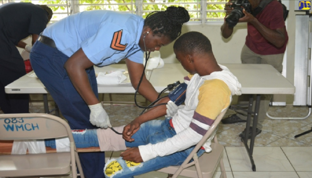 Emergency Medical Services Staff of the Jamaica Fire Brigade (JFB), Corporal Taneisha Drummond (left), provides healthcare to Cooke Street resident, Tyreke Johnson, at a relief shelter during the flood-simulation exercise in Savanna-la-Mar, Westmoreland, on January 7.
