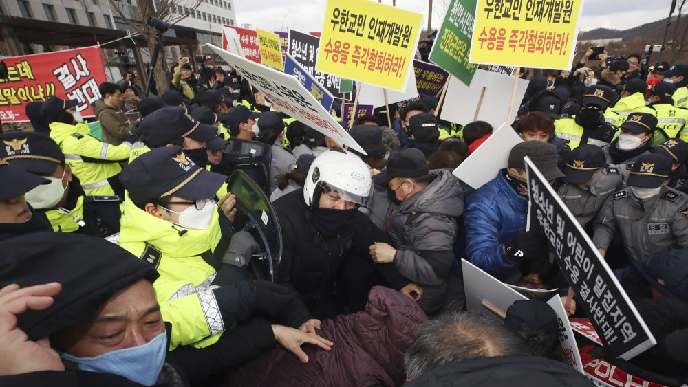 Residents scuffle with police officers during a rally to protest the government's decision to quarantine South Koreans returning from Wuhan in their home town in Jincheon, South Korea, Thursday, Jan. 30, 2020. (Lim Hun-jung/Yonhap via AP)