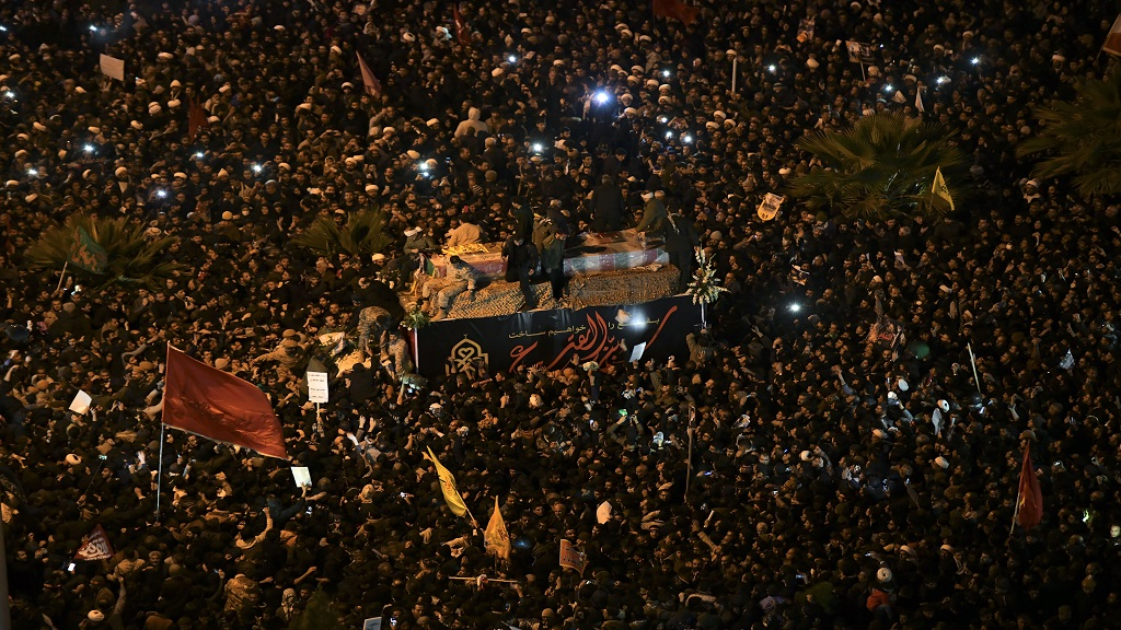 Mourners surround a truck carrying the flag draped coffins of Gen. Qassem Soleimani and his comrades in the holy city of Qom south of the capital Tehran, Iran, Monday, Jan. 6, 2020. (Amir Hesaminejad/Tasnim News Agency via AP)