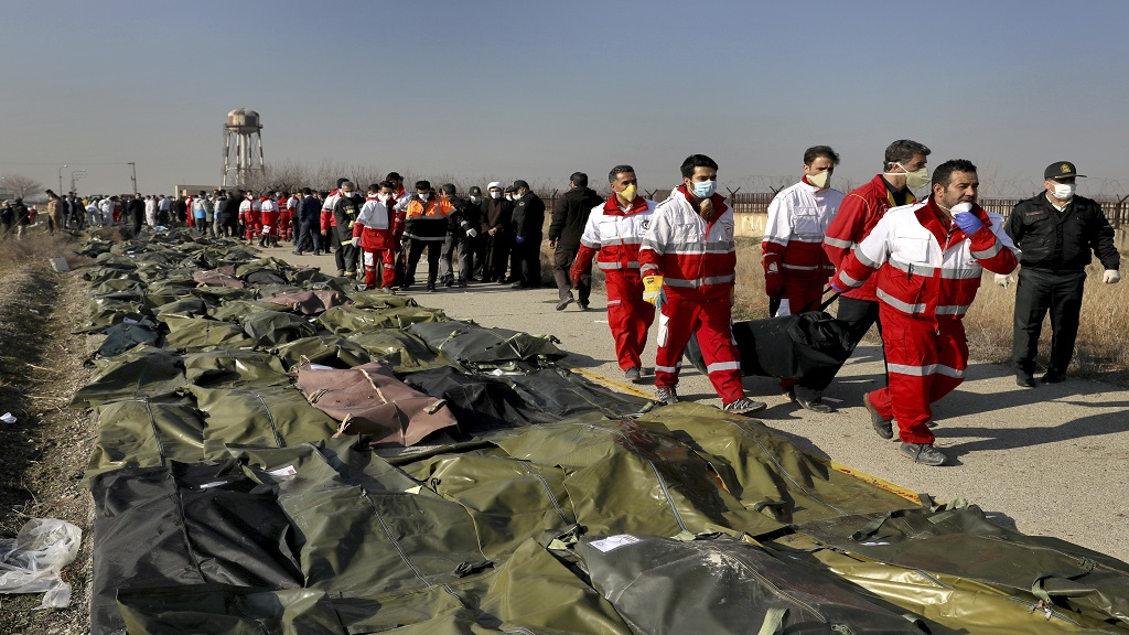 Rescue workers carry the body of a victim of a Ukrainian plane crash in Shahedshahr, southwest of the capital Tehran, Iran, Wednesday, Jan. 8, 2020. (AP Photo/Ebrahim Noroozi)