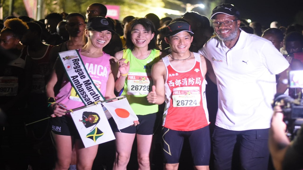 Reggae Marathon race director Alfred Francis (right) shares a light moment with participants from Japan at the start line on Sunday. (Photos: Marlon Reid)