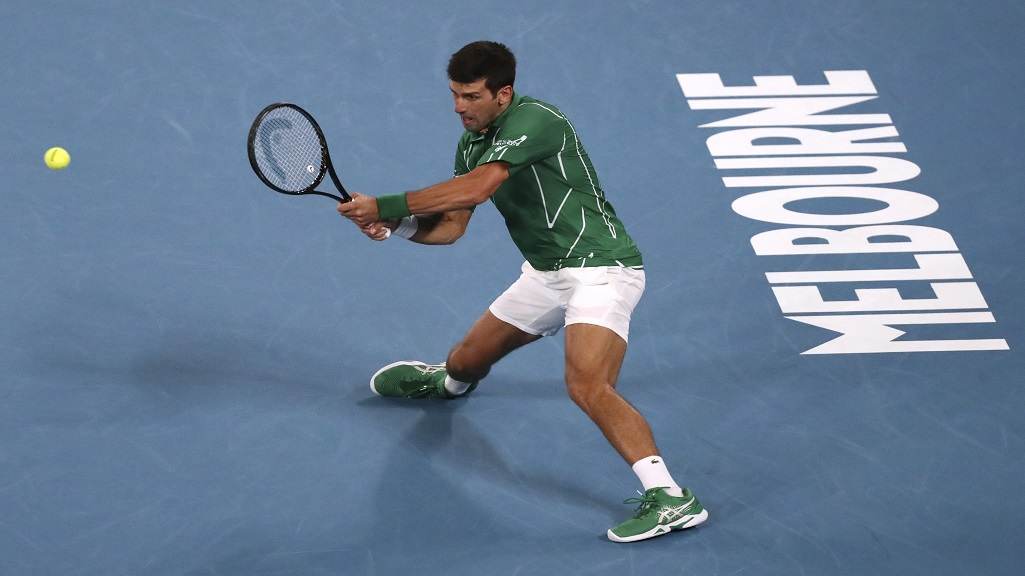 Serbia's Novak Djokovic makes a backhand return to Canada's Milos Raonic during their quarterfinal match at the Australian Open tennis championship in Melbourne, Australia, Tuesday, Jan. 28, 2020. (AP Photo/Dita Alangkara).