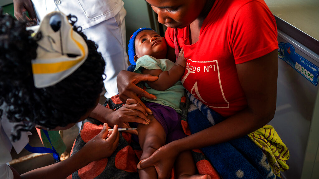 In this photo taken Tuesday, December 10, 2019, residents of the Malawi village of Migowi have their young children become test subjects for the world's first vaccine against malaria. (AP Photo/Jerome Delay)