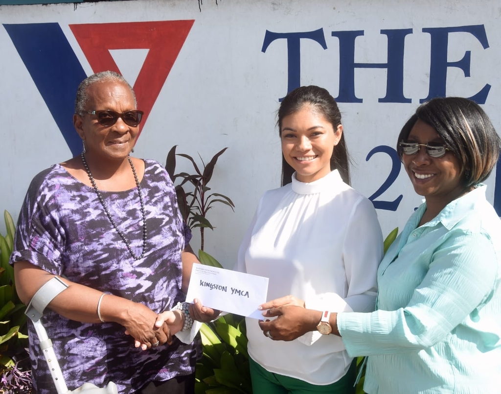Sarah Newland-Martin (left), Administrator & General Secretary of The Kingston YMCA and Hilary Perkins (right), Administrative Assistant at The Kingston YMCA shows appreciation, as Stephanie Harrison (center), Digital and Marketing Manager Mayberry Investments Limited hands over a cheque from the organization in support of youth development programs at The Kingston YMCA, Hope Road.