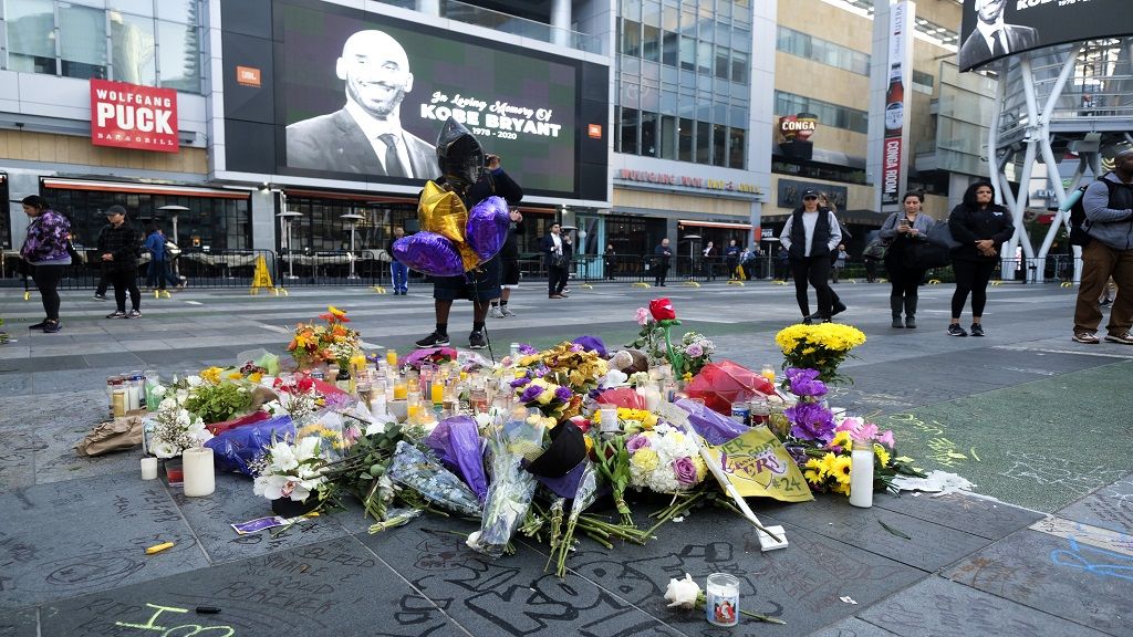 Flowers and candles are placed at a memorial for Kobe Bryant near Staples Center Monday, Jan. 27, 2020, in Los Angeles. Bryant, the 18-time NBA All-Star who won five championships and became one of the greatest basketball players of his generation during a 20-year career with the Los Angeles Lakers, died in a helicopter crash Sunday. (AP Photo/Ringo H.W. Chiu)