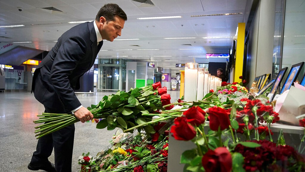 In this handout photo provided by the Ukrainian Presidential Press Office, Ukrainian President Volodymyr Zelenskiy lays flowers at a memorial of the flight crew members of the Ukrainian 737-800 plane that crashed on the outskirts of Tehran. (Ukrainian Presidential Press Office via AP)