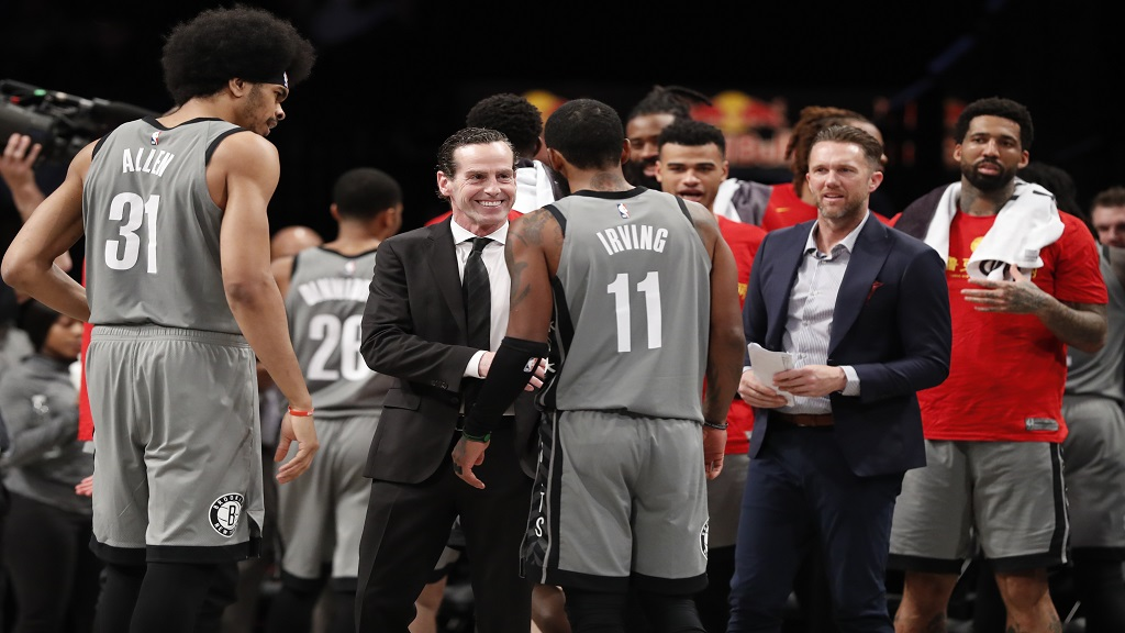 Brooklyn Nets head coach Kenny Atkinson smiles as he talks to Nets guard Kyrie Irving (11) during a timeout in the second half of an NBA basketball game against the Detroit Pistons, Wednesday, Jan. 29, 2020, in New York.