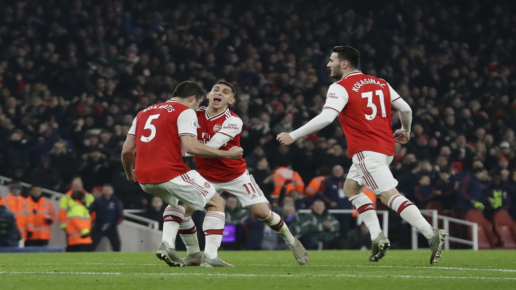 Arsenal's Sokratis Papastathopoulos, left, celebrates with teammate Lucas Torreira and Sead Kolasinac, right, after scoring against Manchester United during their English Premier League football match at the Emirates Stadium in London, Wednesday, Jan. 1, 2020. (AP Photo/Matt Dunham).