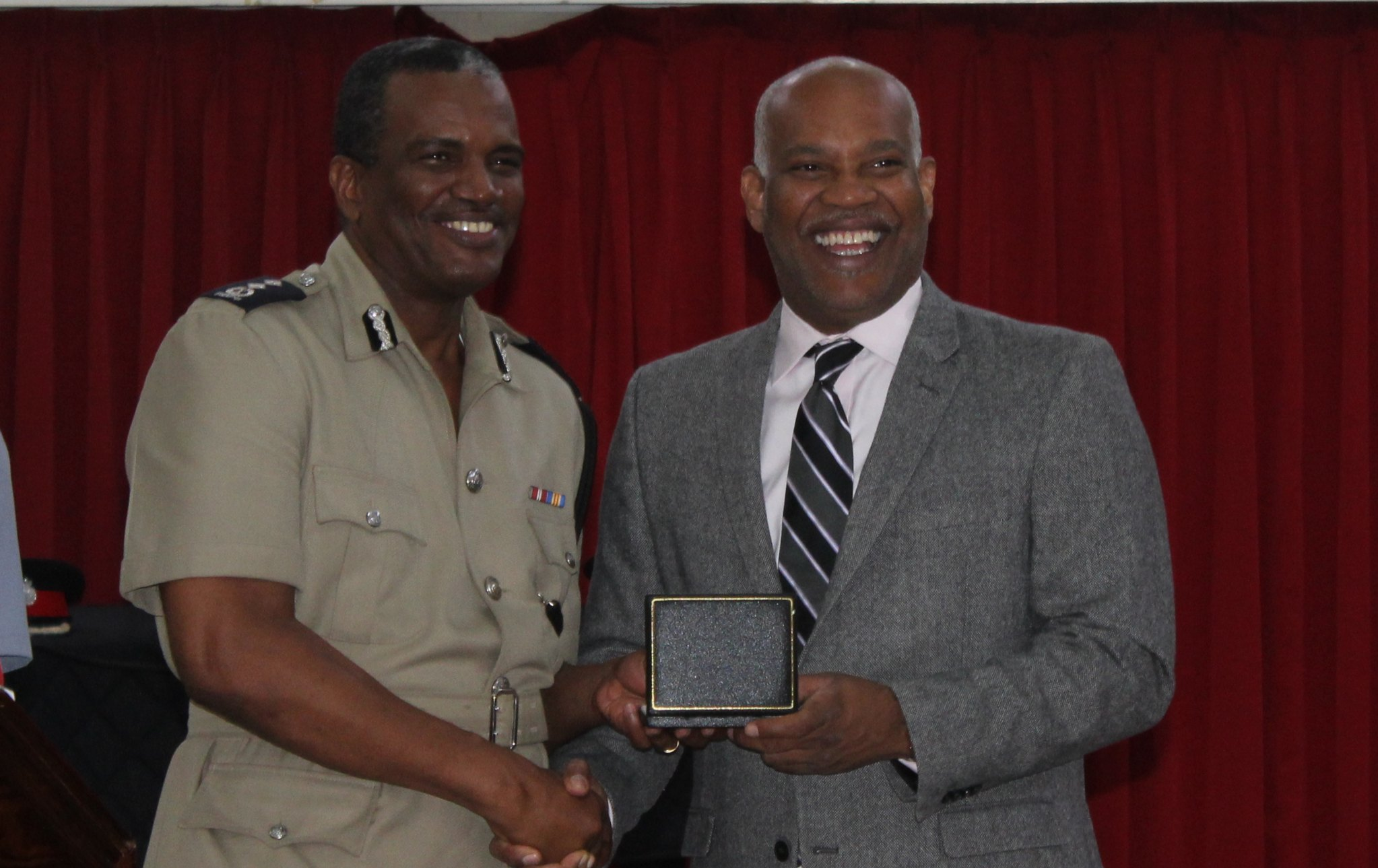Deputy Commissioner, Erwin Boyce (left) receiving medal from Attorney General, Dale Marshall.
