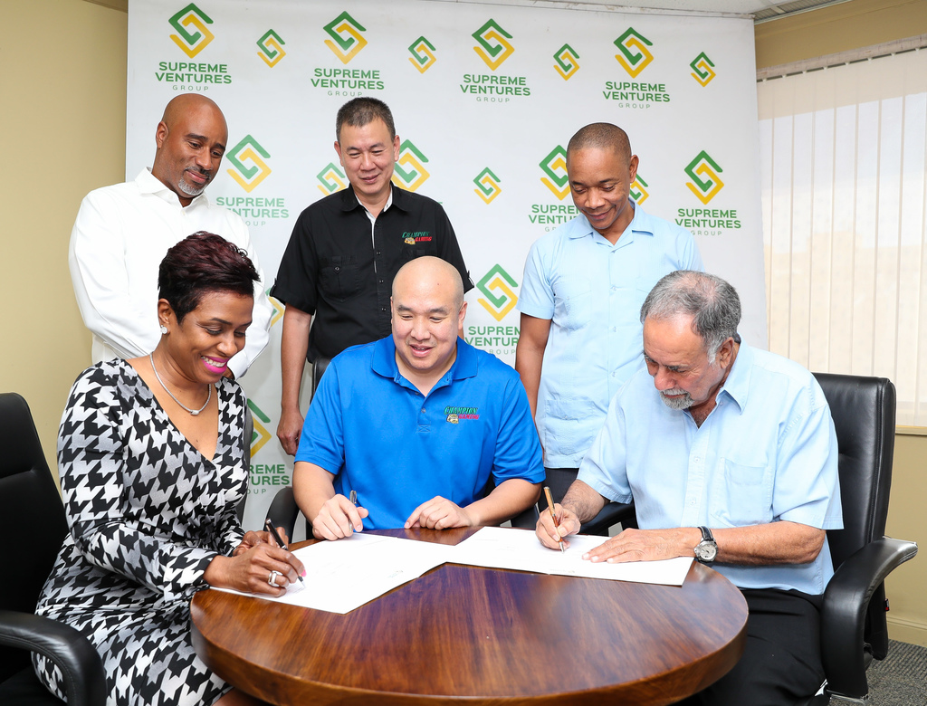 President & CEO, Supreme Ventures Group, Ann-Dawn Young Sang (seated left) signs the agreement to close the deal acquiring the assets of Champion Gaming by Supreme Ventures through its subsidiary, Bingo Investments. Looking on is Champion Gaming Chairman Damian Chin-You (centre) and beside him is Deputy Chair of Supreme Ventures, Ian Levy. Standing are Co-CEO, Prime Sports Jamaica Limited (subsidiary of SVG), Xesus Johnston (left) and Co-CEO of Shared Services, Dennis Chung.